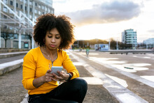 Beautiful Woman Listening Music And Using Smart Phone While Sitting On Steps