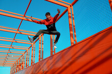Carefree Young Man With Arms Outstretched Jumping On Bridge Against Clear Blue Sky