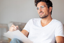 Thoughtful Man With Paper Looking Away While Sitting At Home