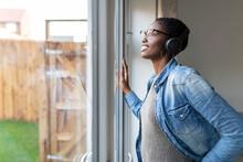 Woman With Headphones Looking Through Window