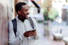 Man With Backpack And Mobile Phone Looking Away While Leaning On Wall