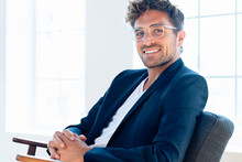 Confident Businessman Wearing Eyeglasses Sitting With Hands Clasped On Armchair At Home