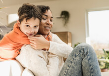 Smiling Boy Embracing Mother While Playing At Home