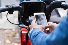 Hands Of Man Using Smart Phone For Renting Bicycle At Parking Station
