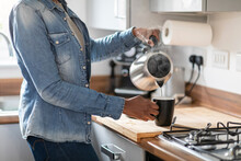 Woman Pouring Water From Kettle Into Mug In Kitchen
