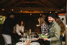 Portrait Of Smiling Man Holding Leafy Bowl While Friends Arranging Dining Table During Party