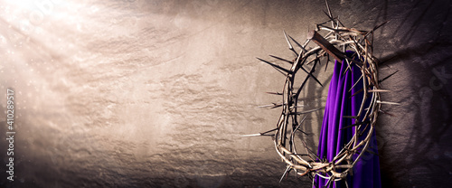Canvas Print Crown Of Thorns And Purple Robe Hanging On Nail In Stone Wall With Light Rays