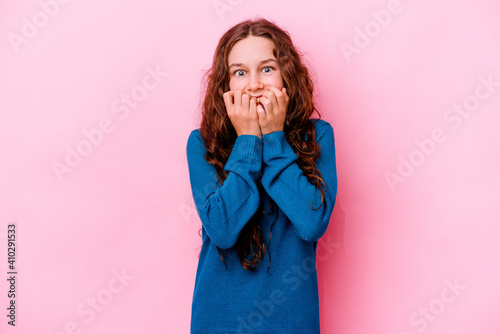 Fotografia, Obraz Little caucasian girl isolated on pink background biting fingernails, nervous and very anxious