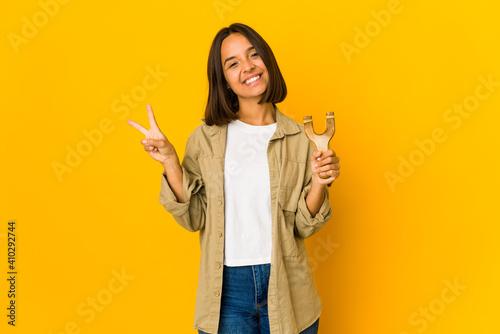 Valokuva Young hispanic woman holding a slingshot joyful and carefree showing a peace symbol with fingers