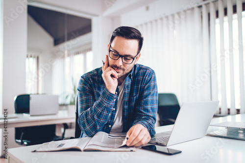 Businesman reading newspapers at work