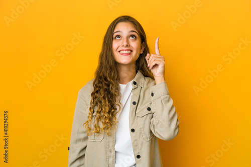 Young caucasian woman indicates with both fore fingers up showing a blank space Fototapeta