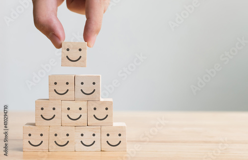 Papel de parede Hand putting wooden cube block shape with icon face smiley, The best excellent b