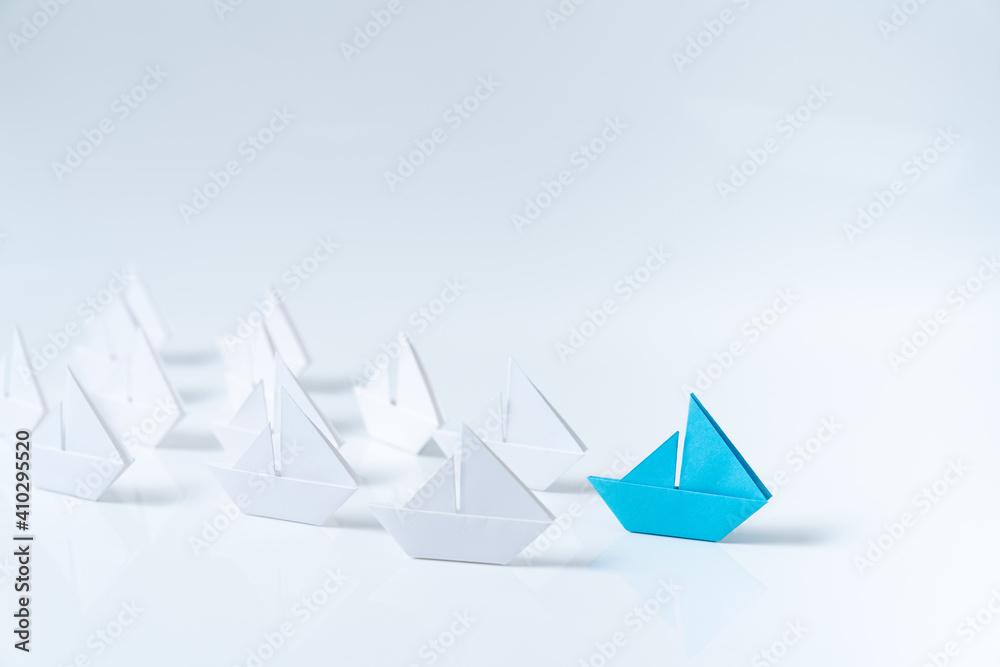 Fototapeta Leadership or leader concept using a blue paper ship leading among white ships