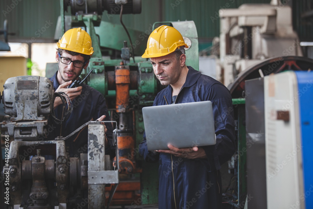 Fototapeta worker using digital laptop while supervising production at plant, copy space.  workers using machine equipment in factory