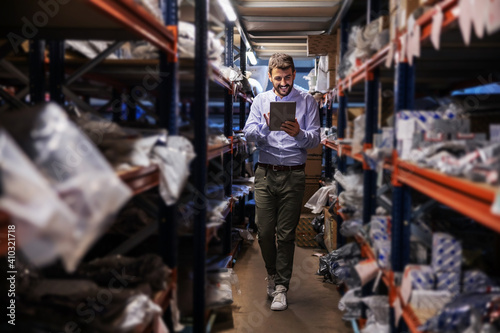 Obraz Full length of bearded supervisor walking trough storage of export firm, checking on goods and using tablet. - fototapety do salonu