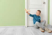 Cute Little Boy With Wooden Airplane Sitting Near Closed Door