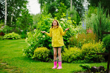 Happy Kid Girl In Yellow Raincoat Playing And Having Fun In Summer Garden Under The Rain