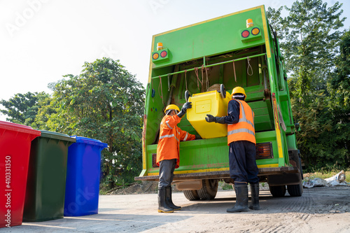 Fototapety, obrazy: Two refuse collection workers loading garbage for trash removal.