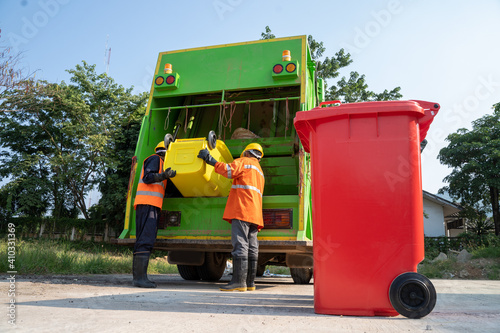 Fototapety, obrazy: Garbage man working together on emptying dustbins for trash removal.