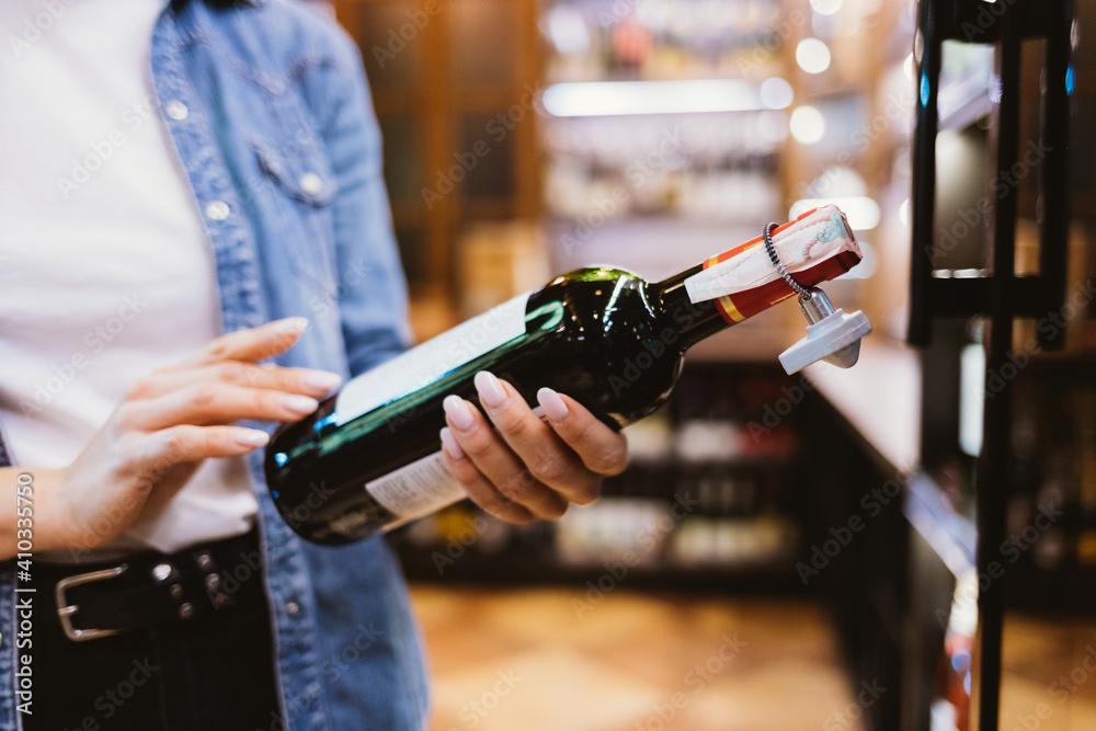 Fototapeta Close-up female hands holding bottle of wine