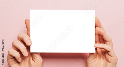 Obraz Female hands hold a blank sheet of paper on a pink background. Advertising space - fototapety do salonu