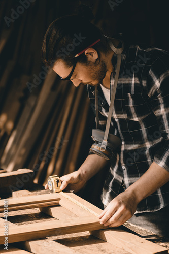 Fotografering Carpenter man attend to making masterpiece woodworks handcrafted furniture fine measure in wood workshop, Vertical shot