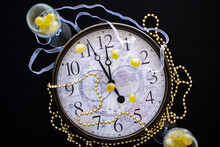A Clock Face Showing Just Before Midnight On New Years Eve In Spain With Two Champagne Flutes With Twelve Grapes