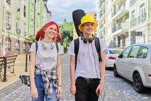 Teenagers Guy And Girl Walking And Talking Along City Street With Guitar In Case