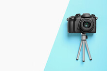 Modern Camera And Mini Tripod On Color Background, Flat Lay With Space For Text. Video Production Equipment