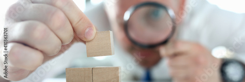 Obraz na plátne Close-up of man looking on wooden cubes stack through magnifying glass