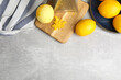 Lemon zest and fresh fruits on grey table, flat lay. Space for text