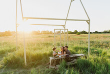 Young Parents And Little Son Eat Cake Together In A Field At Sunset.