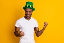 Portrait Of Delighted Afro American Guy Win Saint Patrick Contest Raise Fists Scream Yes Wear Green Hat White Clothes Isolated Over Bright Shine Color Background