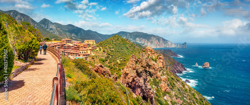 Tourists walk to the Nebida town. Panoramic morning view of Sardinia island, Italy, Europe. Aerial spring seascape of Mrditerranean sea. Traveling concept background.