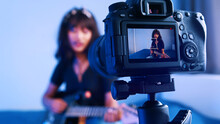 Young Woman Playing Guitar In Front Of The Camera. Streaming Online Class. High Quality Photo