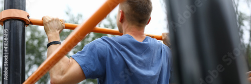 Obraz Close-up of strong male pulls up on street horizontal bar. Person in blue shirt training outdoors. Sporty guy exercise for fit body. Health and hobby. Sport and active lifestyle concept - fototapety do salonu