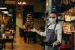 canvas print picture - waitress welcomes guests in restaurant or cafe