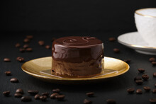 Austrian Cake, Sackertorte. Chocolate Cake On A Golden Plate. Coffee Beans On A Black Textured Table. White Cup With Cappuccino. Side View Of A Chocolate Dessert.