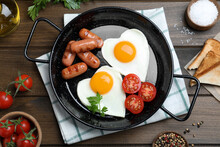 Romantic Breakfast With Fried Sausages And Heart Shaped Eggs On Wooden Table, Flat Lay. Valentine's Day Celebration