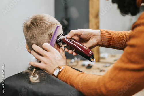 Obraz the process of cutting a blond boy with a long braid in a chair in a barbershop salon, a barbershop concept for men and boys - fototapety do salonu