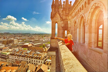 Blonde Tourist Girl Pointed Rooftops Of Geneva Skyline From Height Of The North Tower Of Cathedral Gothic Romanesque Of Saint-Pierre, French Swiss In Switzerland. Sunset Light Between Mountains.