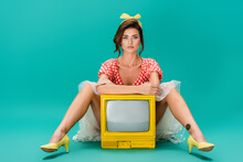 Young Pin Up Woman Looking At Camera While Sitting Near Bright Yellow Vintage Tv On Turquoise