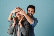 Young Brunette Excited Man Covering Eyes Of Surprised Girl