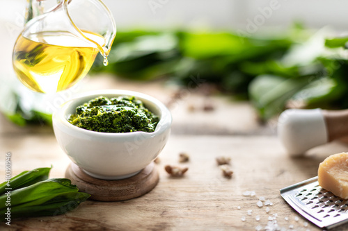 Obraz na plátně Wild leek pesto with olive oil and parmesan cheese in a white ceramic mortar on a wooden table