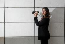 Manager Donna Mora,  Vestita In Tailleur Nero, Tiene In Manodei Binocoli, Isolata Su Sfondo Muro Bianco Di Mattonelle Rettangolari