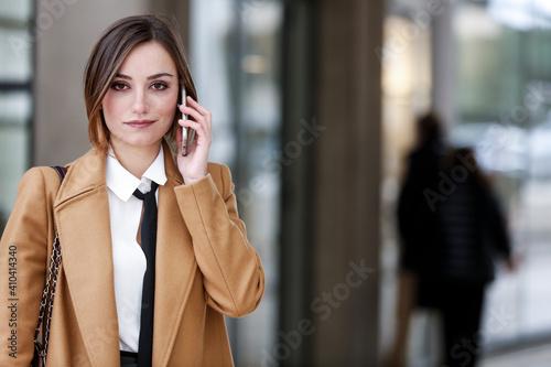Fotografie, Obraz manager donna con cappotto beige , camicia bianca e cravatta nera cammina in con