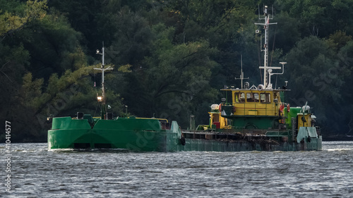 Obraz na plátně SCOW ON THE WATERWAY - A barge flowing along the canal against the background of