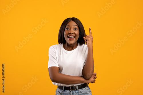 Inspired black woman raising finger up, having idea © Prostock-studio