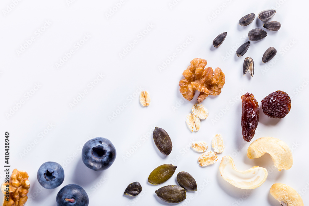 Fototapeta Seeds of sunflower, nuts, fruits and dried fruits on white background with copy space.