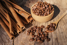 Coffee Beans In The Bowl And The Top Cinnamon Sticks Are Placed On Wooden Table.